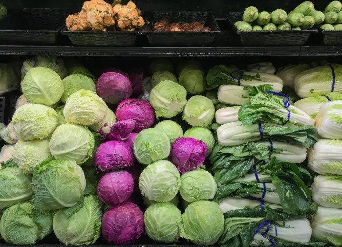 Капуста белокочанная и фиолетовая на полке в магазине