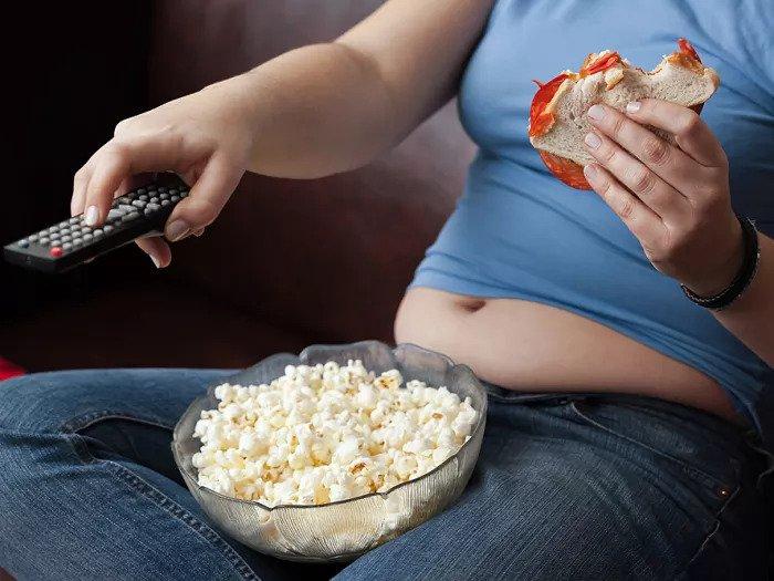 Женщина с животом сидит перед телевизором с едой