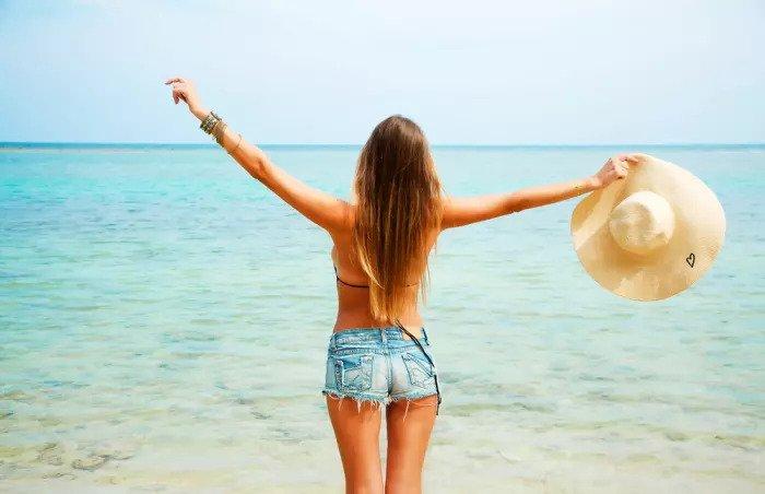 Молодая женщина в коротких джинсах на пляже