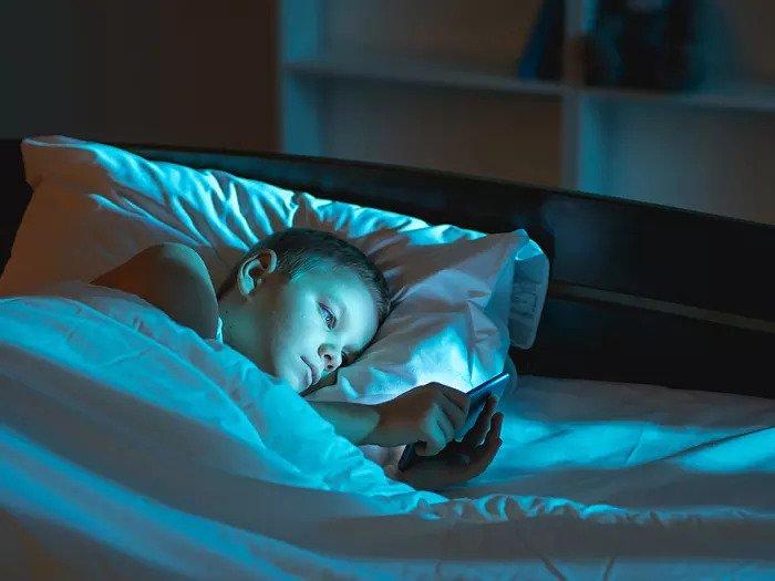 Мальчик с телефоном в кровати