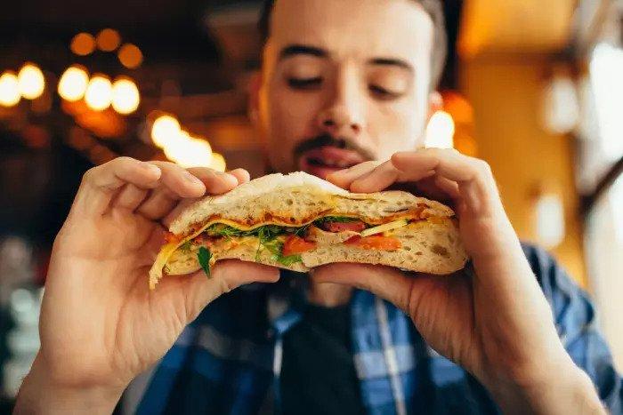 Мужчина ест бутерброд