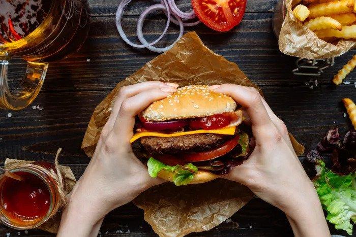 Пара рук держит гамбургер