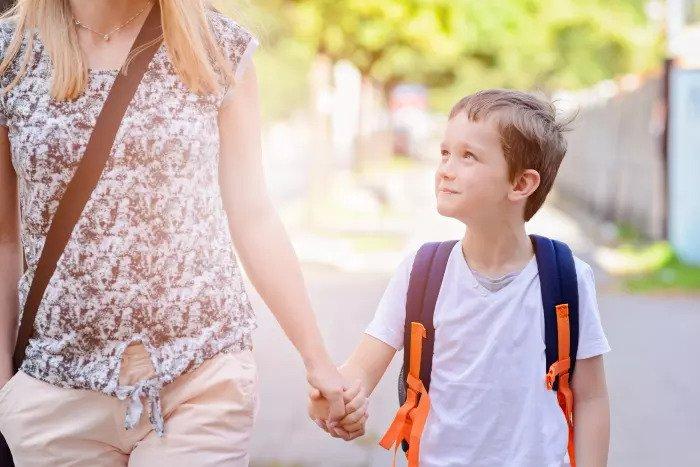 7-летний мальчик держит руку своей матери