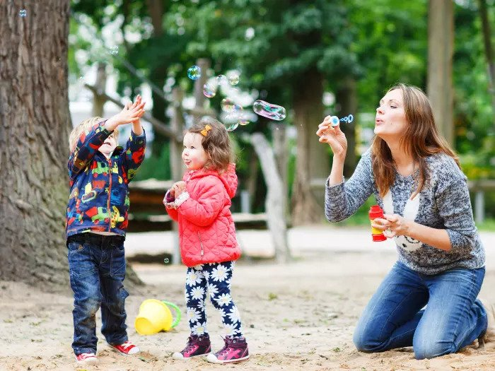Мама и двое детей пускают мыльные пузыри на улице