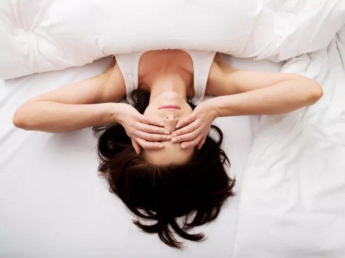 Уставшая женщина лежит в постели