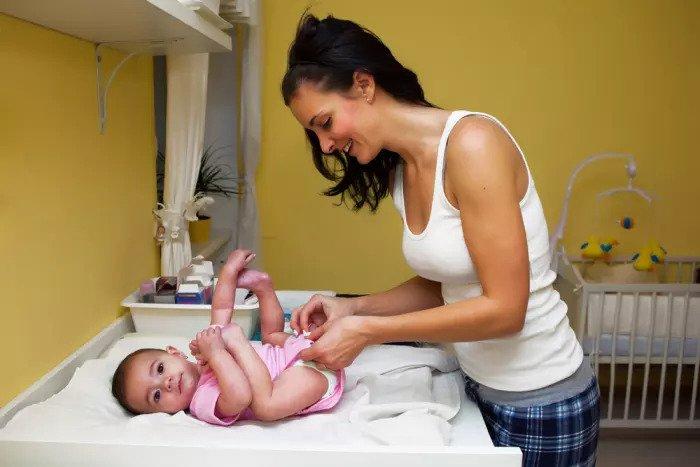 Мать меняет подгузник на ребенка