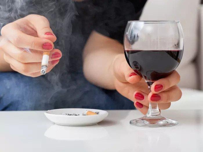 Женщина пьет вино и курит сигарету