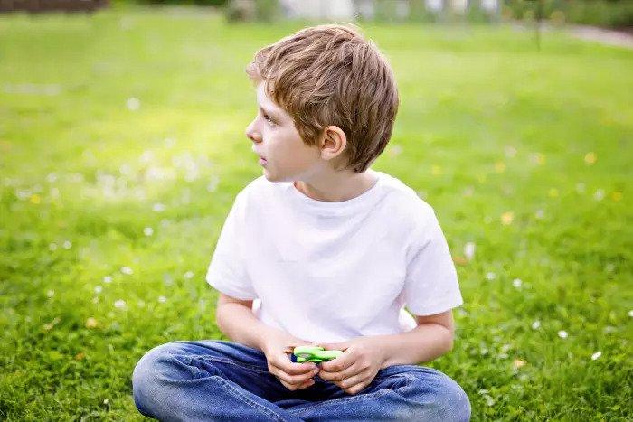 Мальчик сидит на газоне и держит вертушку
