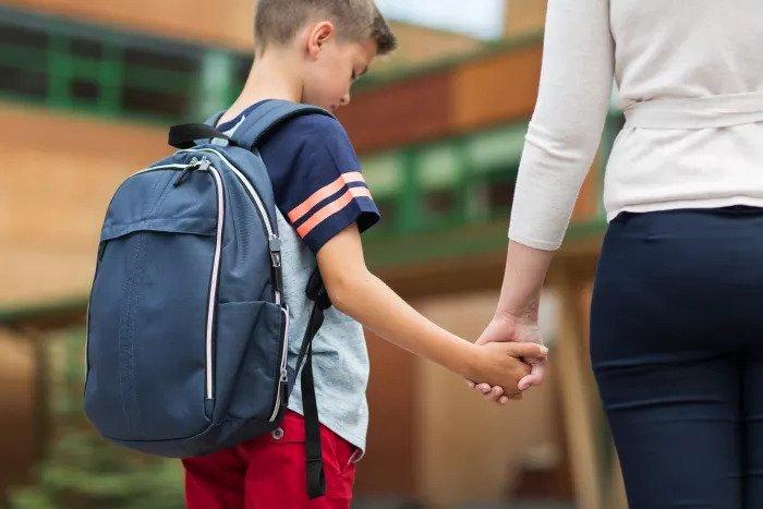 Мать провожает грустного ребенка в школу