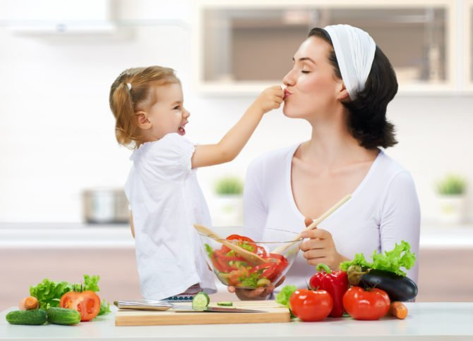 дочка кормит маму овощами
