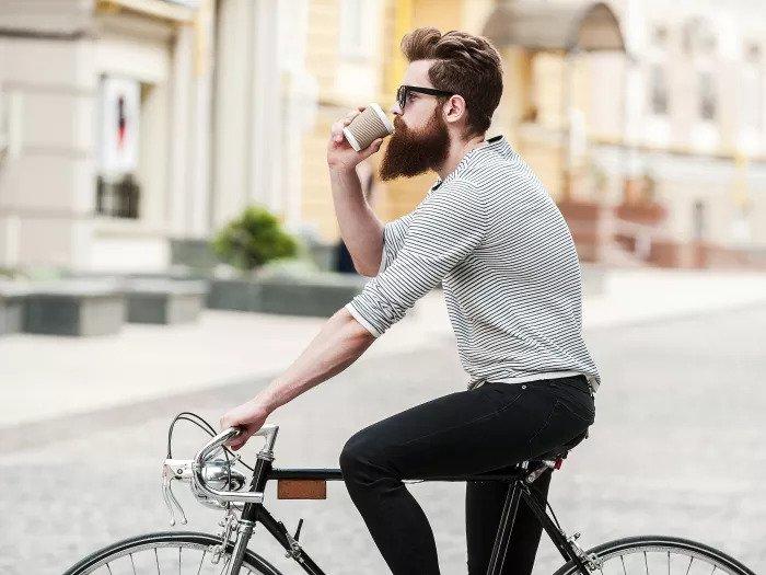 Бородатый мужчина катается на велосипеде и пьет кофе