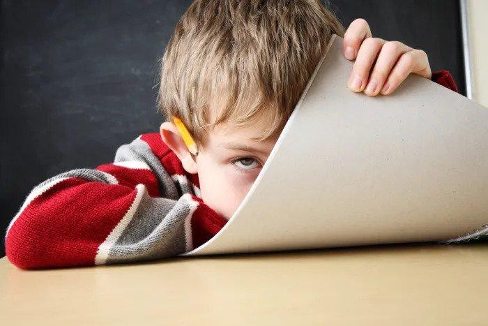 Мальчик прячется за тетрадью в классе
