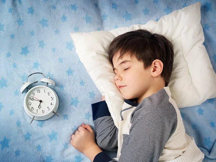 Ребенок спит в постели рядом с будильником