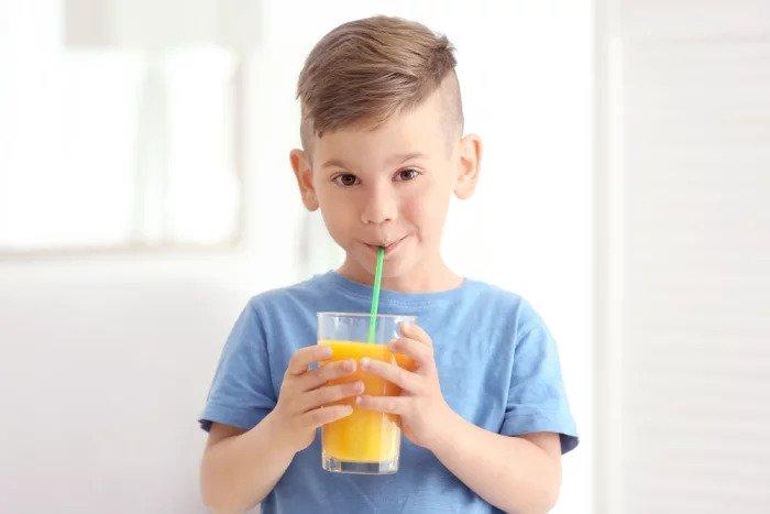 Мальчик пьет апельсиновый сок в соломе