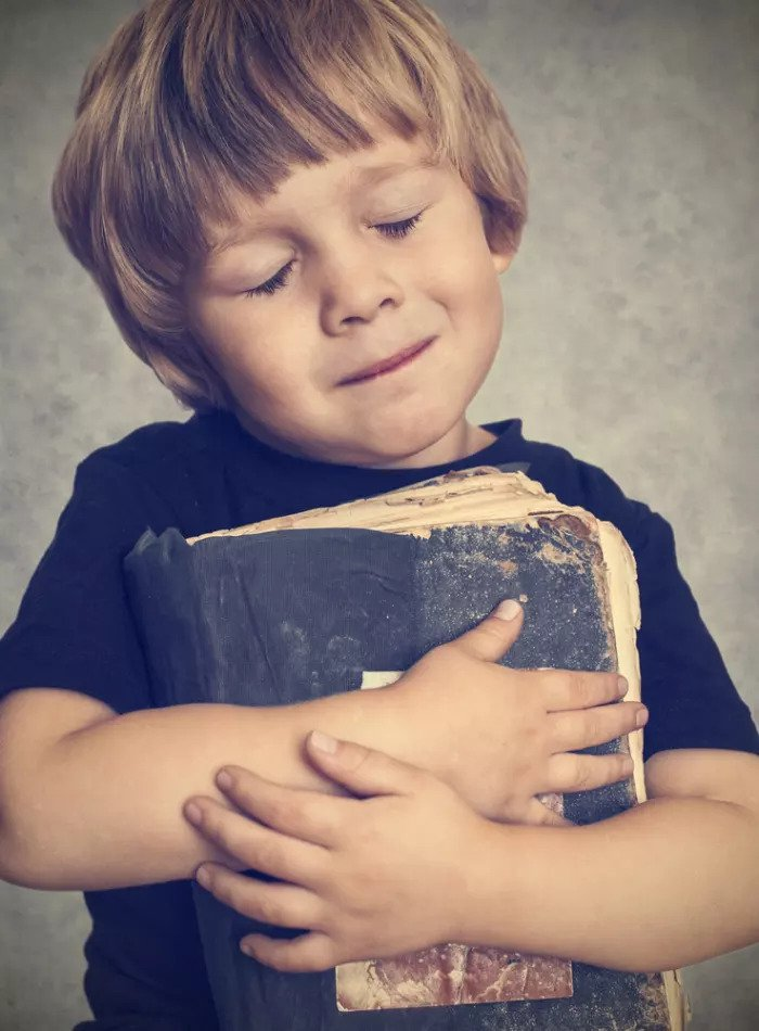 Мальчик обнимает книгу