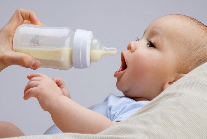 Малыш пьет молочко из бутылочки