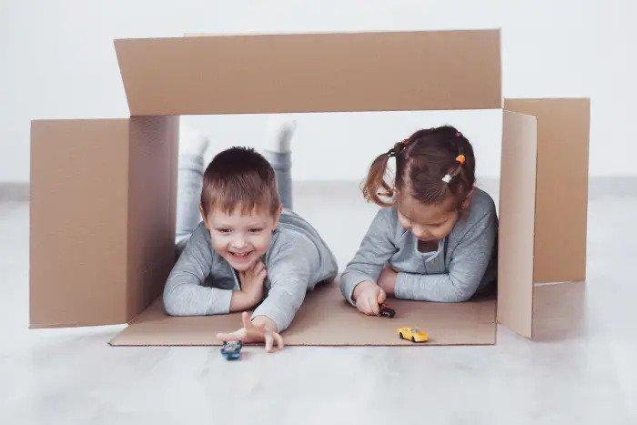 Дети играют в картонной коробке