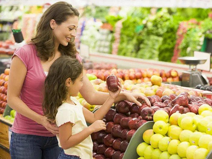 Мать и дочь покупают фрукты в супермаркете