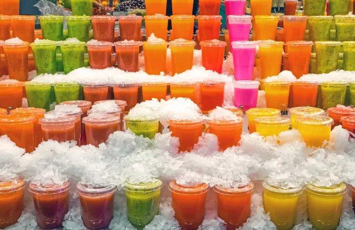 Фруктовые соки на стенде для соков на рынке баккарии в Барселоне