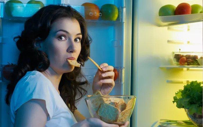 Женщина ест у холодильника