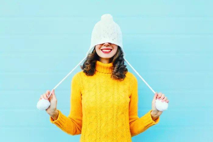 Женщина в желтом свитере и шерстяной шапке на синем фоне