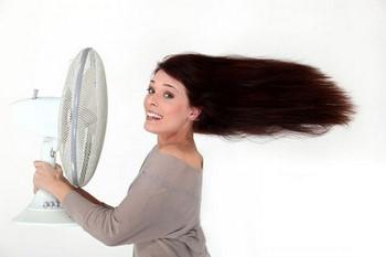 Женщина охлаждается вентилятором