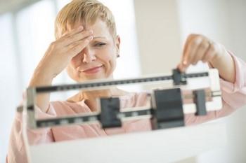 Женщина недовольна своим весом на весах