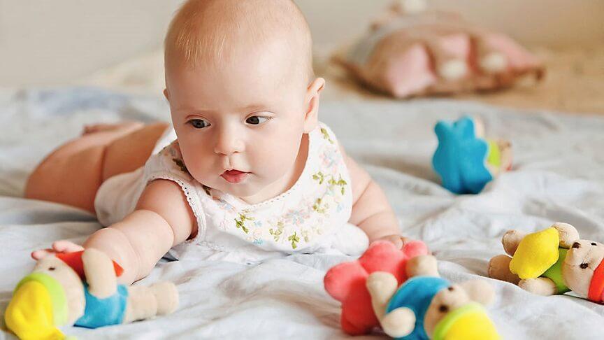 малыш пытается дотянутся до яркой игрушки