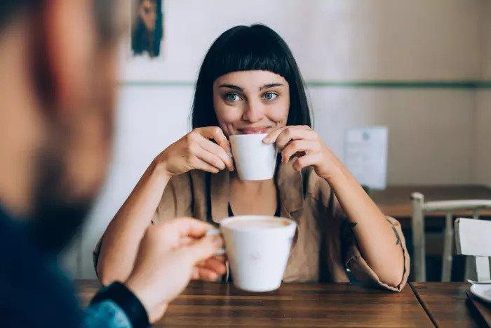 Женщина пьет чашку кофе