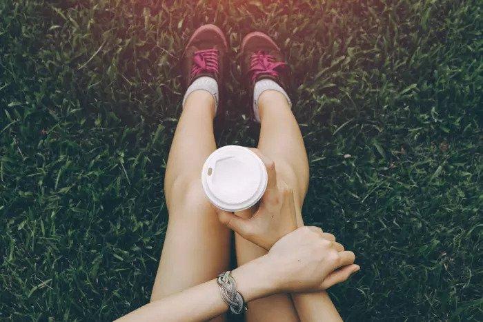 Женщина пьет кофе после тренировки