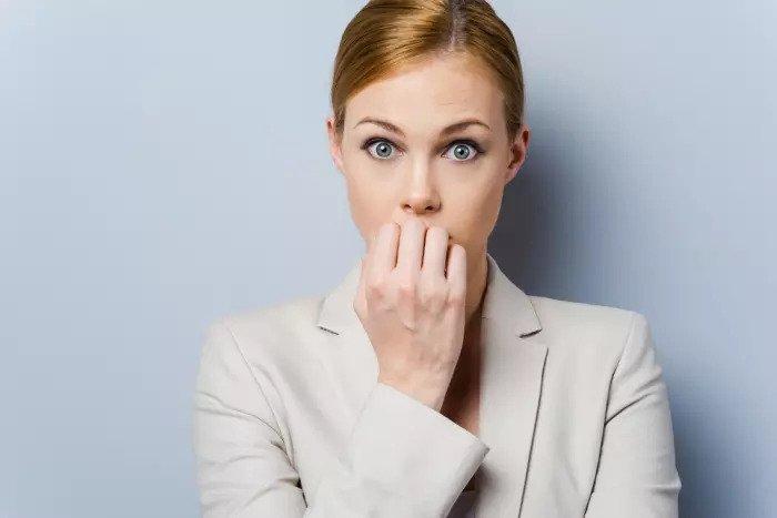 Подчеркнутая женщина кусает ногти