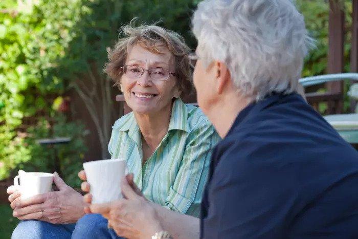 Две взрослые женщины пьют кофе