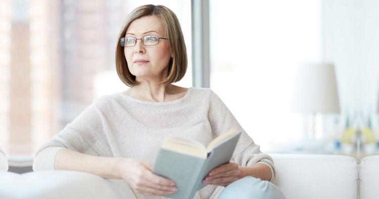 Пожилая женщина читает книгу