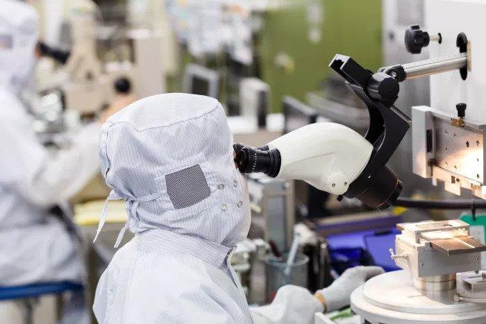 Промышленный рабочий смотрит в микроскоп