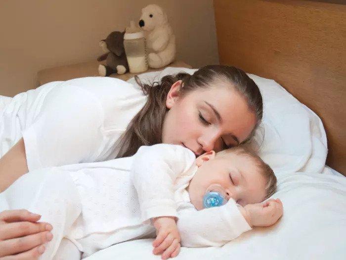 Мать и ребенок спят вместе в постели