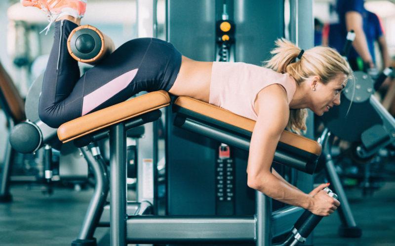 Тренировка в зале: сгибание ног лёжа в тренажёре