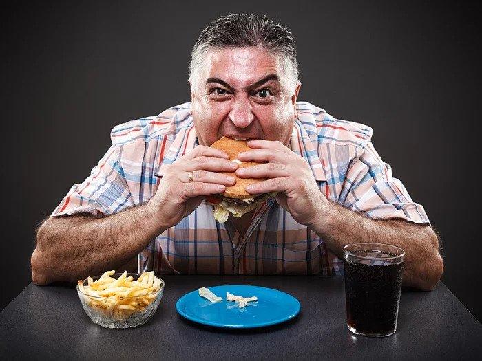Мужчина жует гамбургер