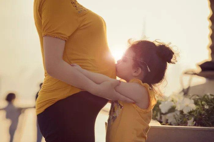 Девочка целует беременный живот своей матери