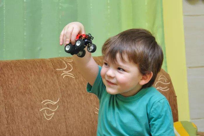 Мальчик играет в игрушечные машинки