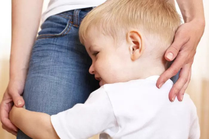 Led застенчивый, обнимая его матери ноги