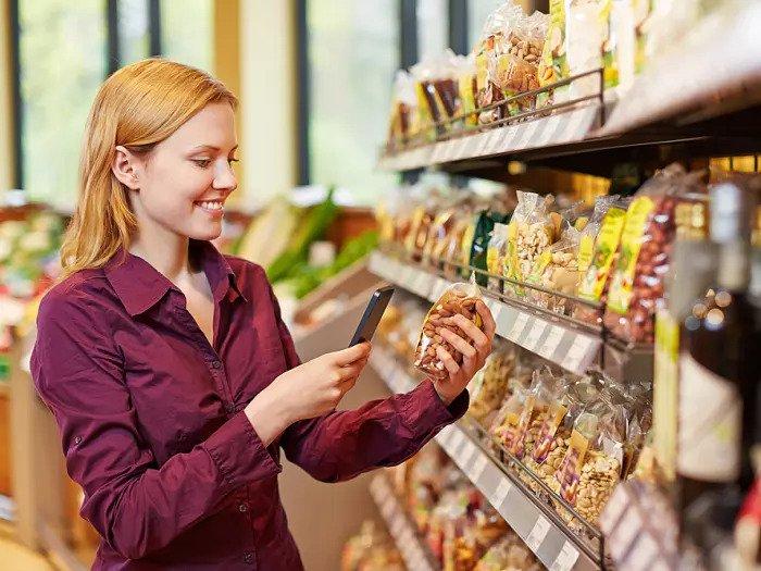 Женщина сканирует штрих-код продуктов в супермаркете