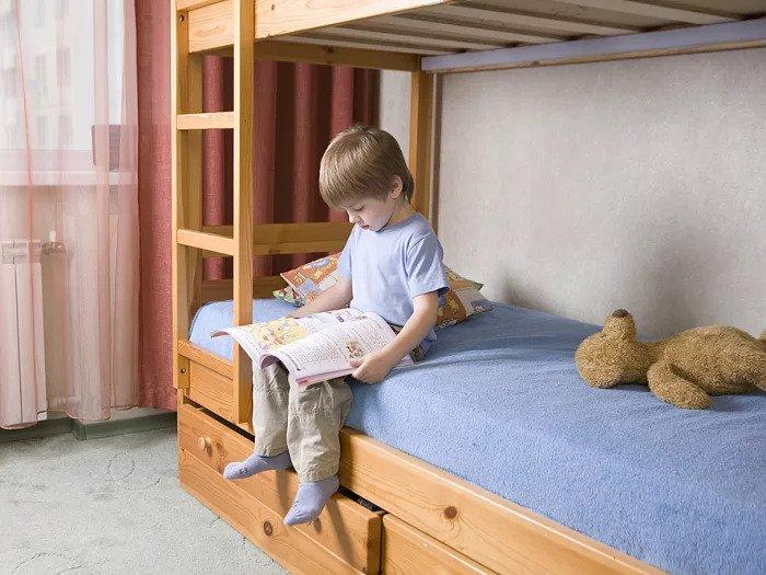 Мальчик читает книгу на двухъярусной кровати