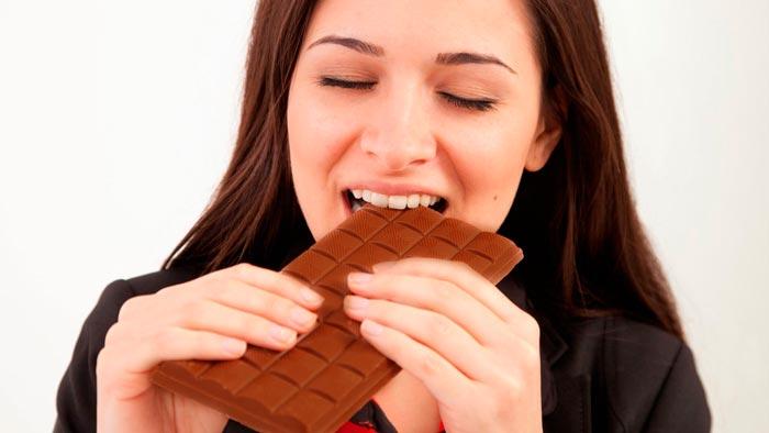 Девушка ест шоколад
