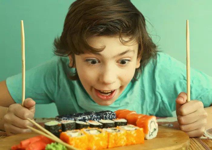 Мальчик ест суши