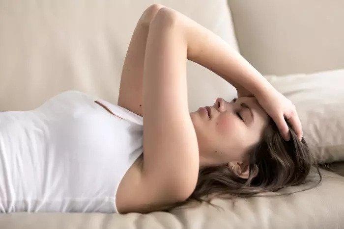 Молодая женщина лежит на диване и держит голову руками