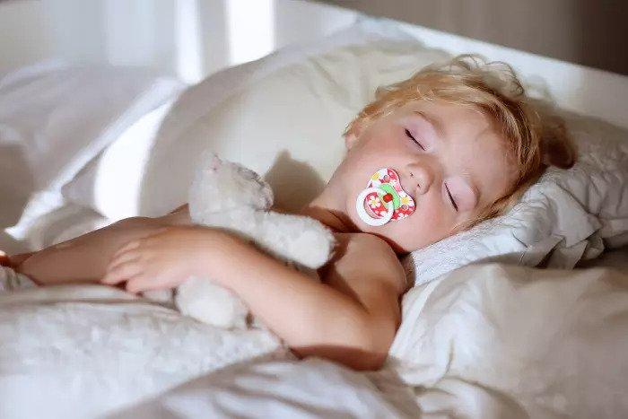 Мальчик спит в постели с соской