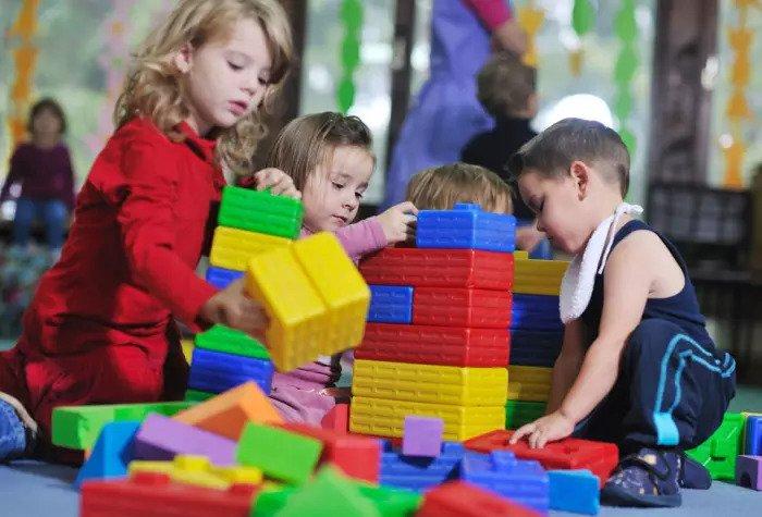 Малыши играют с большими пластиковыми кубиками