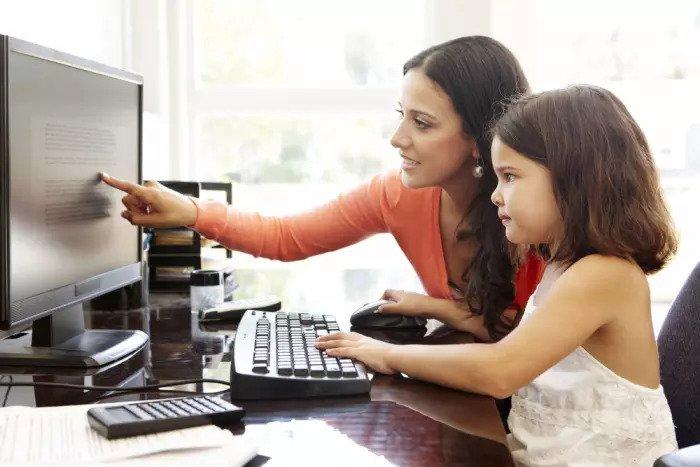 Мать и дитя перед компьютером в офисе